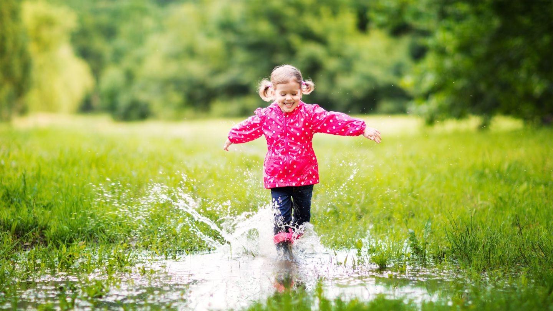 niña jugando con alegria en el lodo