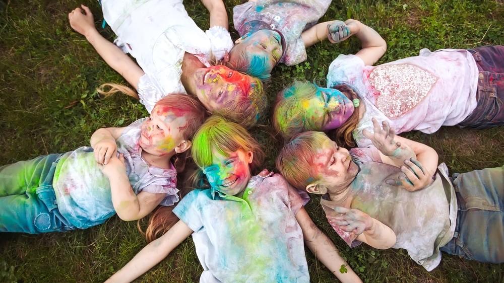 Chicos sucios con pinturas de colores