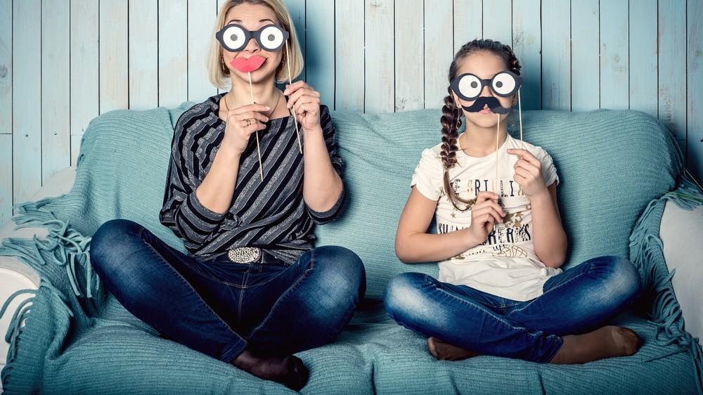 Madre e hija jugando con caretas
