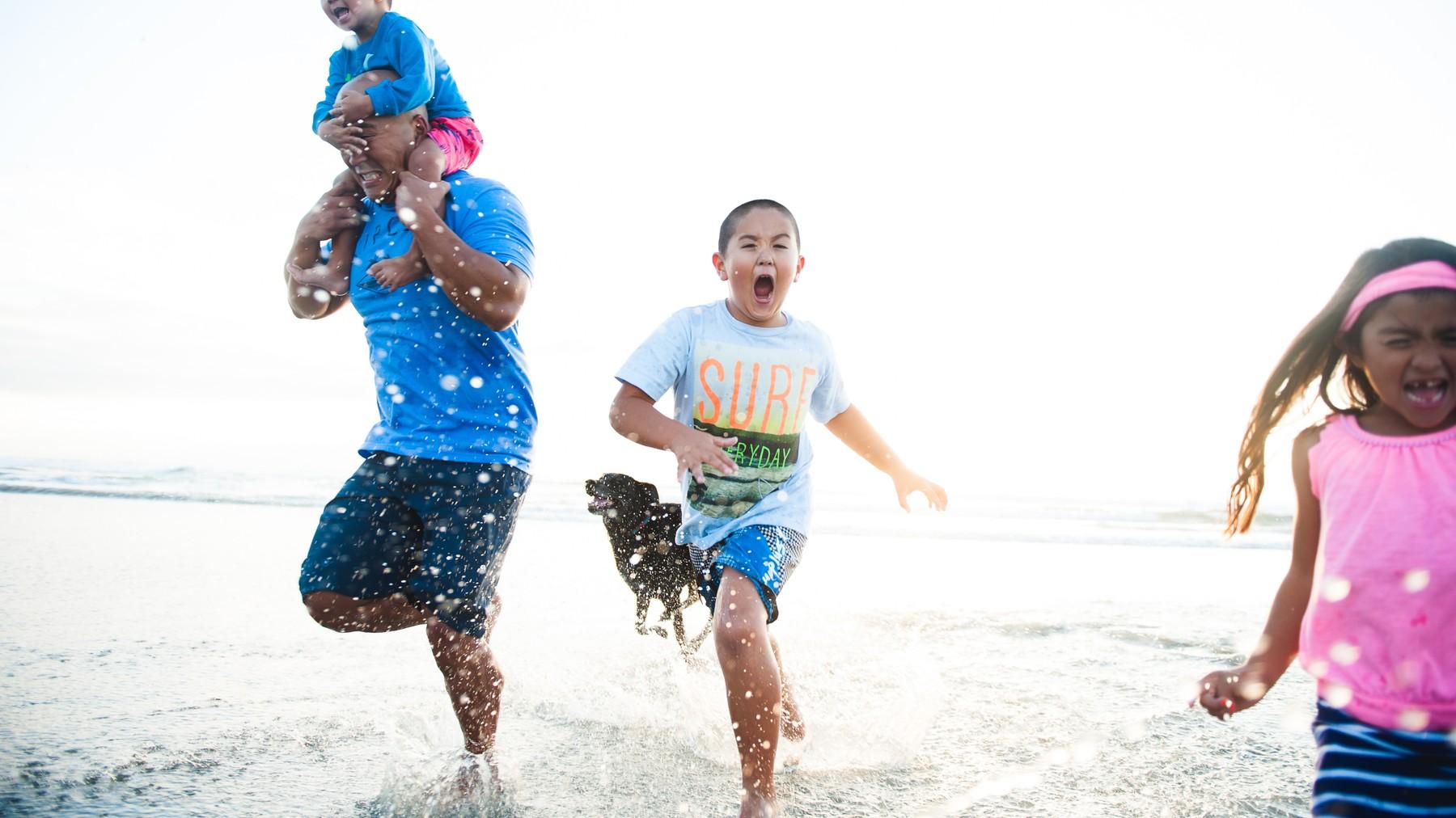 familia juega feliz en la playa
