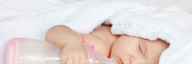 Bebé recién nacida dormida en toalla con biberón