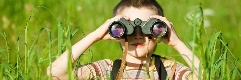 Niño mirando a través de binoculares en un campo