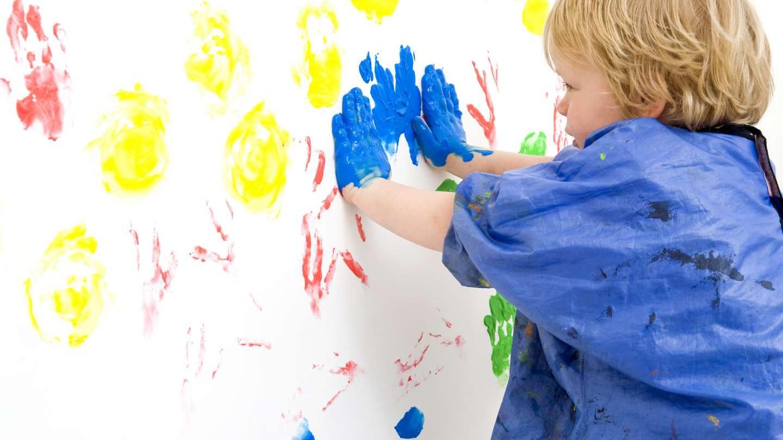 Niño dejando sus huellas con pintura en la pared